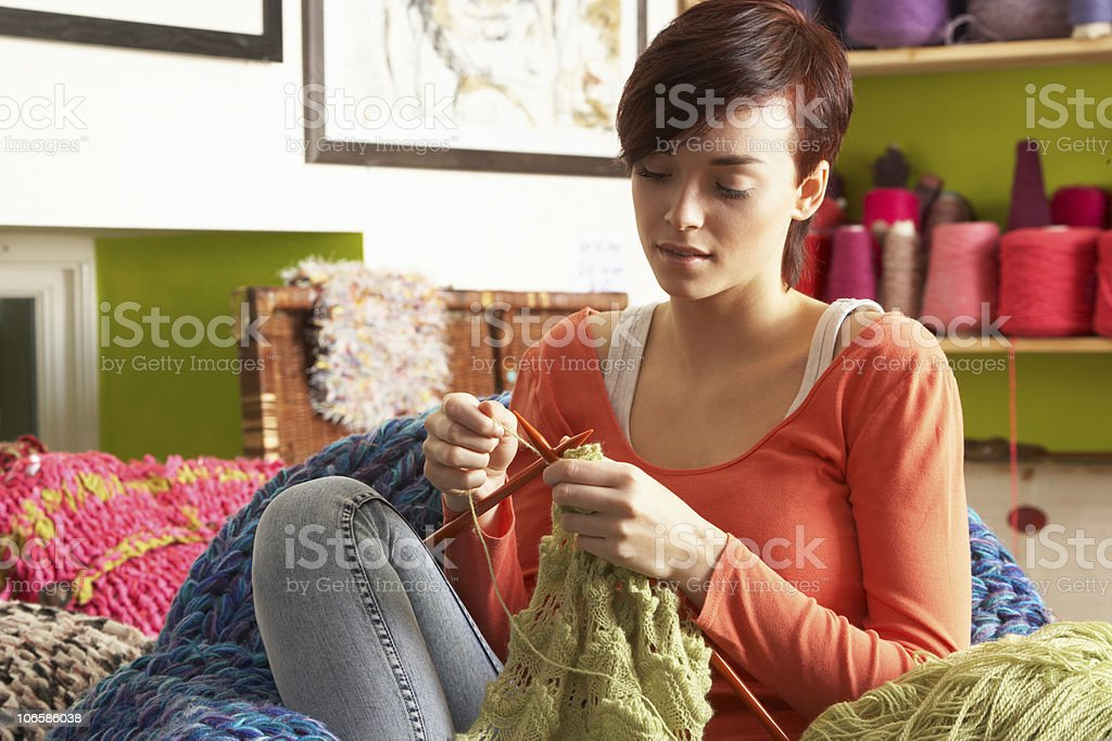 Young woman sitting and knitting an item in green wool stock photo