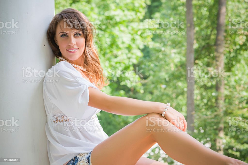 Young woman sitting and leaning against a pillar stock photo