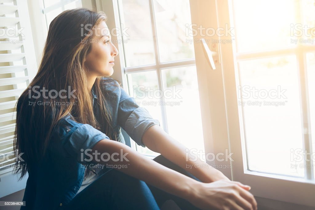 Smiling young woman sitting and looking through the window. With long...