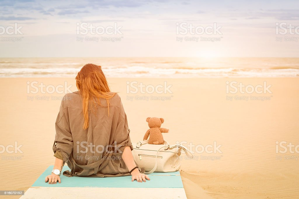 Young woman sitting at beach with teddy bear at sea stock photo