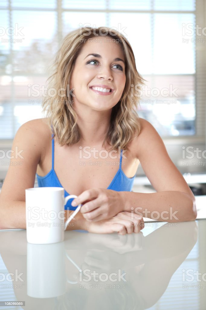 Young Woman Sitting at Counter and Drinking Cup of Coffee royalty-free stock photo