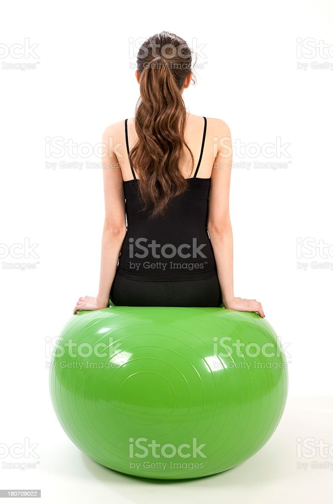 Young woman sitting back against on fitness ball royalty-free stock photo