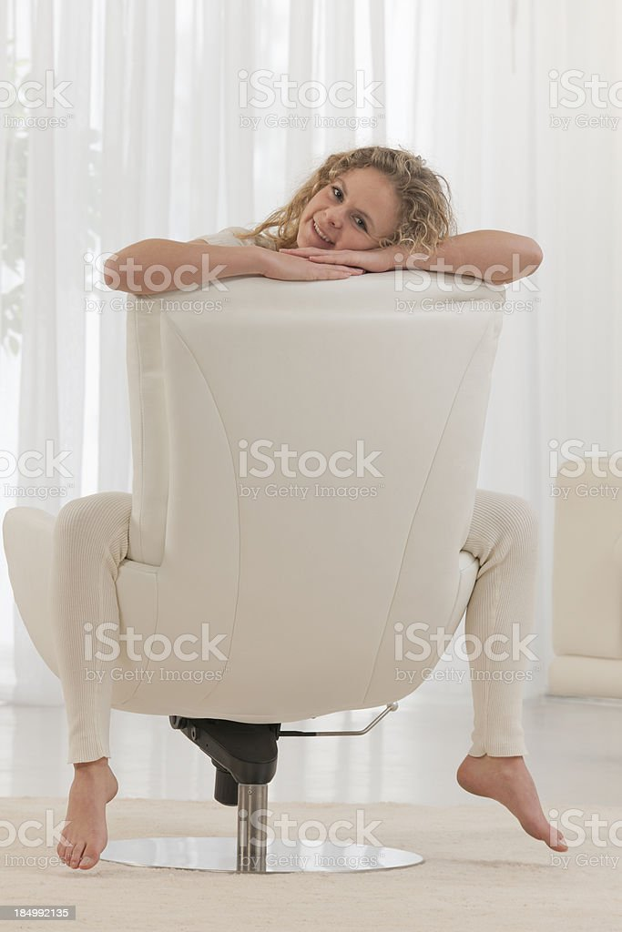 young woman sitting backwards on chair in living room royalty-free stock photo