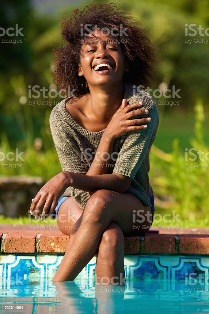 Young woman sitting by pool with feet in water stock photo