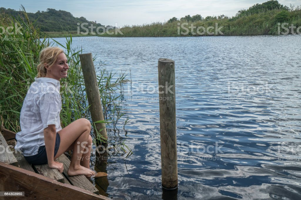Young woman sitting by the river contemplating nature stock photo
