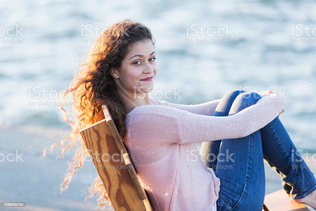 Young woman sitting by the water on a pier stock photo