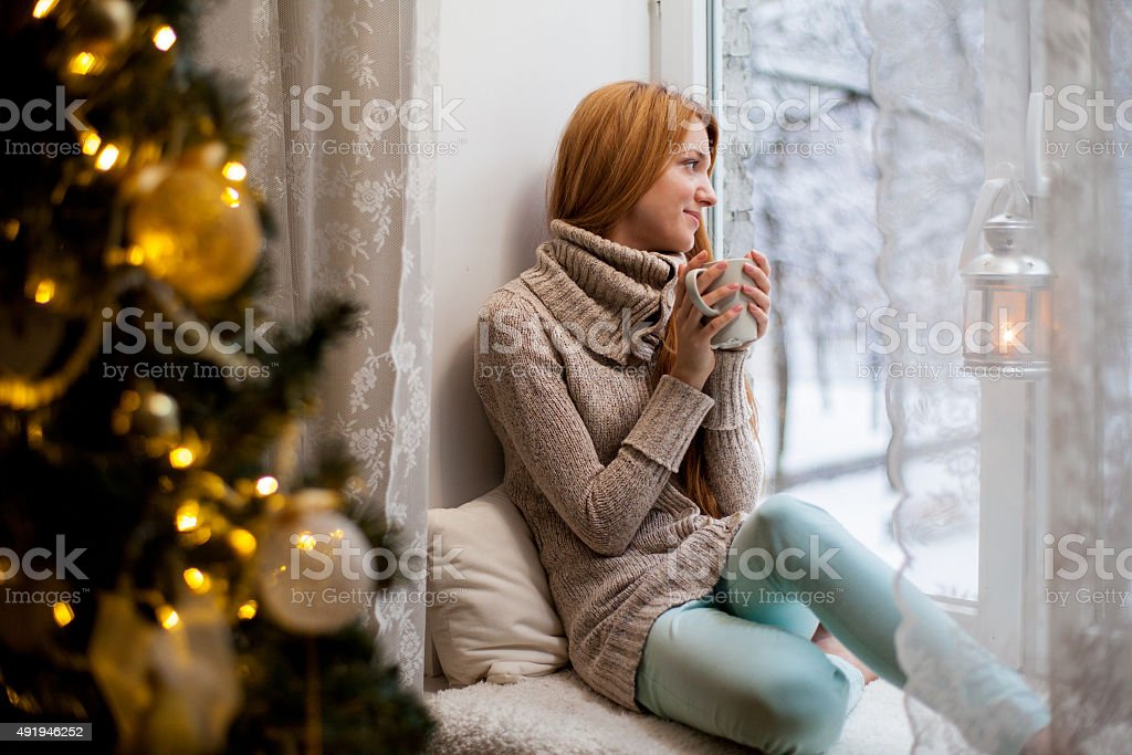 Young woman sitting by the window drinking hot coffee stock photo