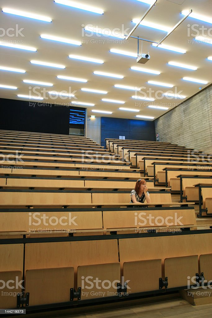 A young woman sitting in an empty lecture room royalty-free stock photo
