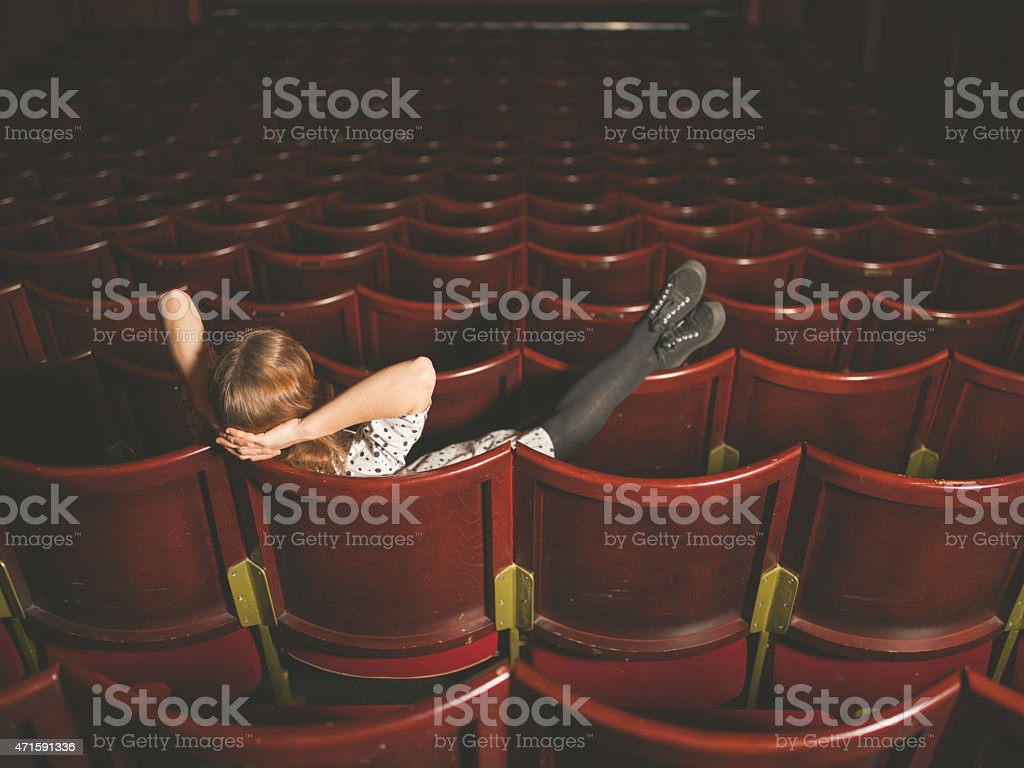 Young woman sitting in auditorium stock photo