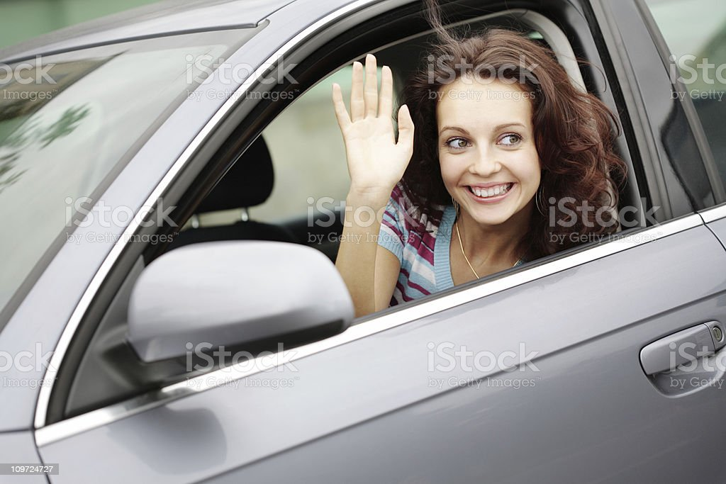 Young Woman Sitting in Car and Waving Out Window royalty-free stock photo