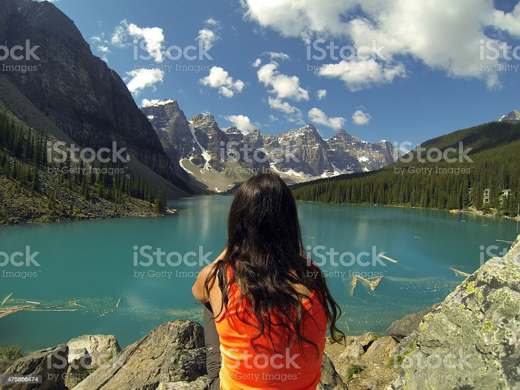 Young woman sitting in front of a turquoise colored lake stock photo