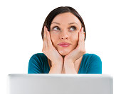 Young woman sitting in front of laptop and thinking