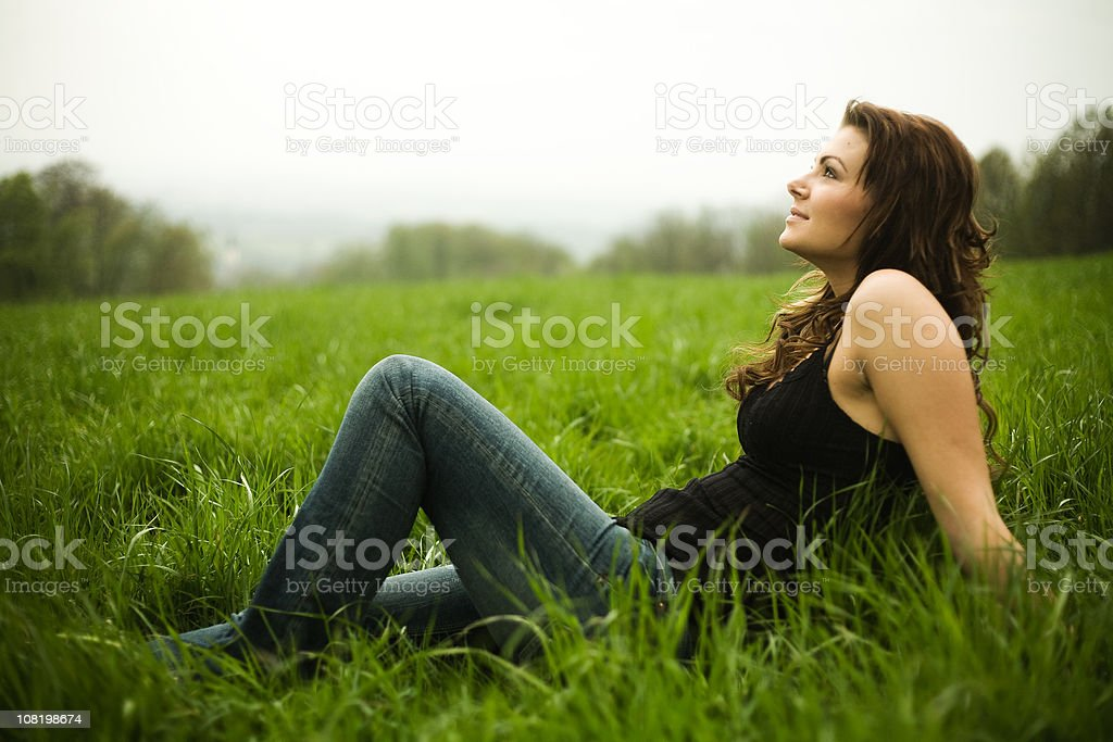 Young Woman Sitting in Grass Field royalty-free stock photo