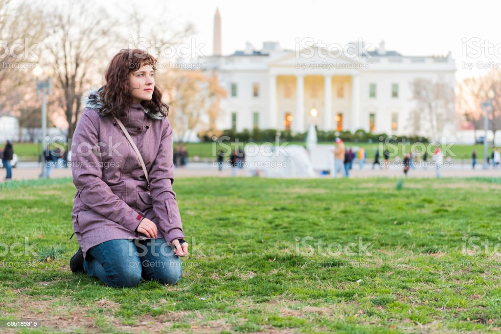 Young woman sitting in grass in park in front of white house at sunset stock photo