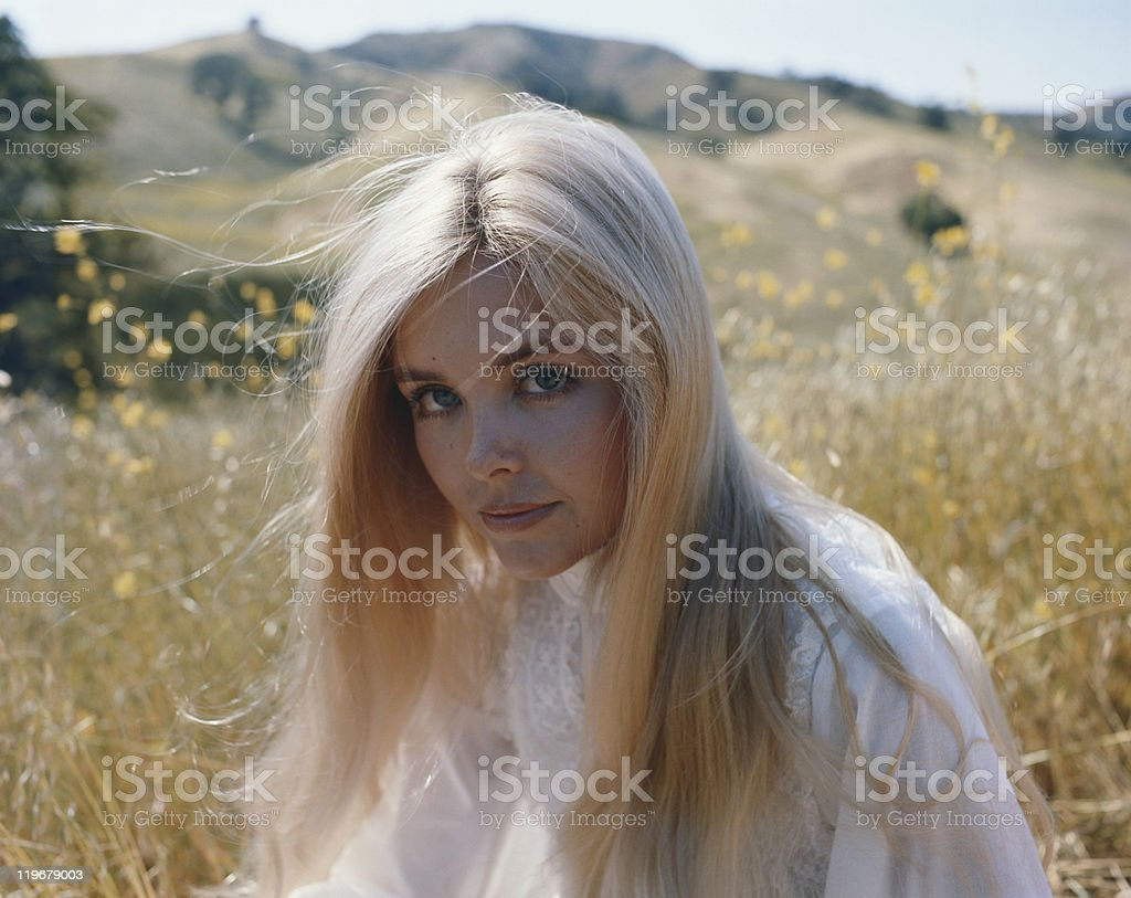 Young woman sitting in grass, portrait royalty-free stock photo