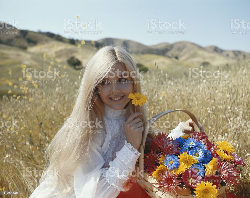 Young woman sitting in grass with wicker basket of flowers, smiling royalty-free stock photo