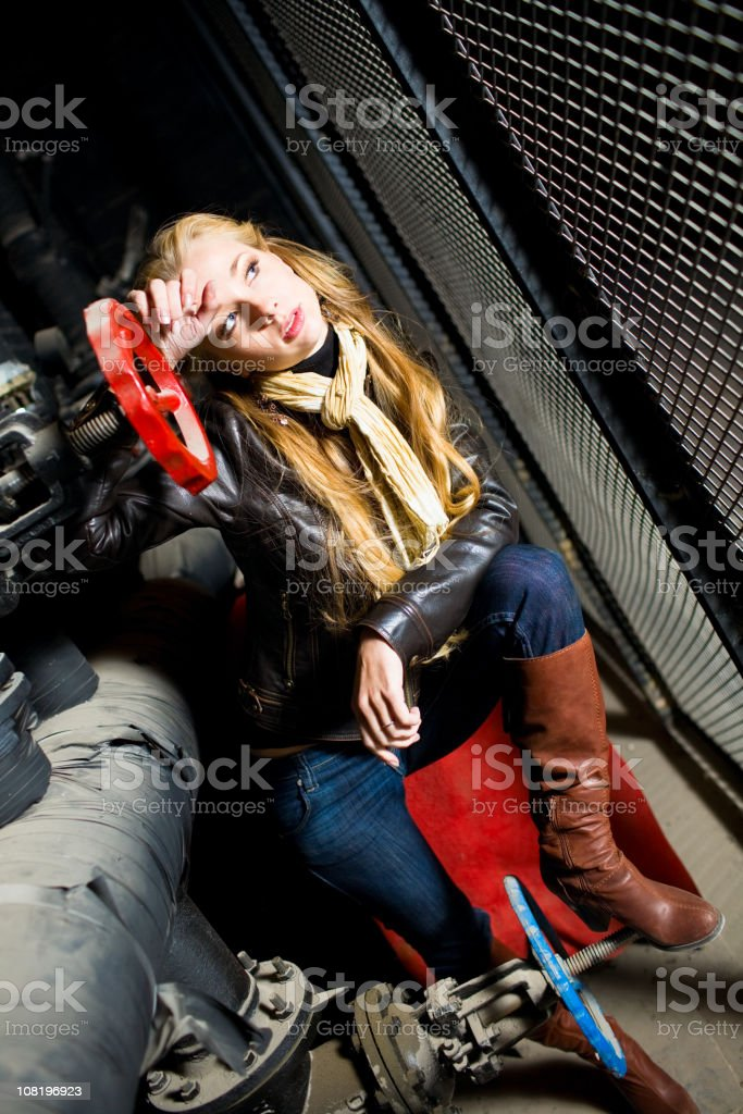 Young Woman Sitting in Industrial Pipes royalty-free stock photo