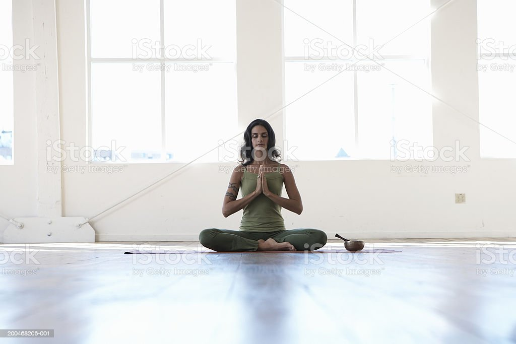 Young woman sitting in lotus position, meditating, eyes closed stock photo