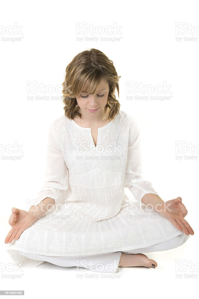 Young woman sitting in meditative pose on a white background royalty-free stock photo