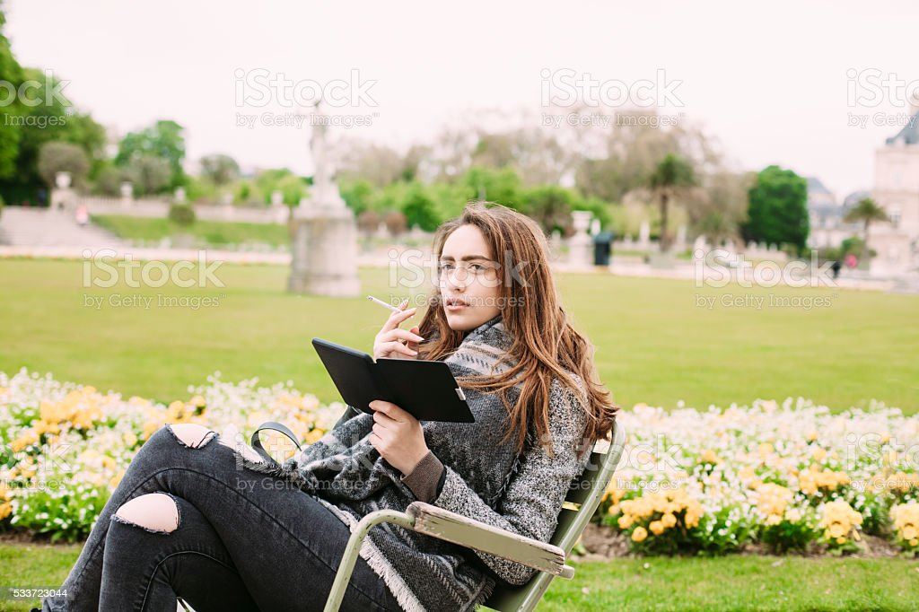 Young woman sitting in park and smoking stock photo