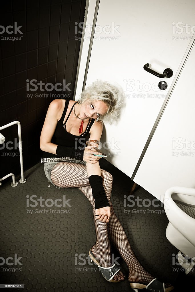 Young Woman Sitting in Restroom Injecting Drugs from Needle royalty-free stock photo
