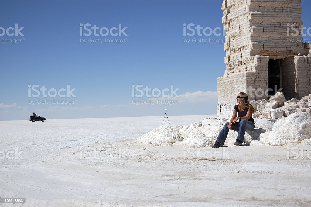 Young woman sitting in salt desert, Bolivia stock photo