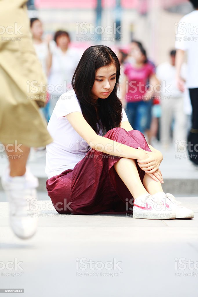 young woman sitting in the street royalty-free stock photo