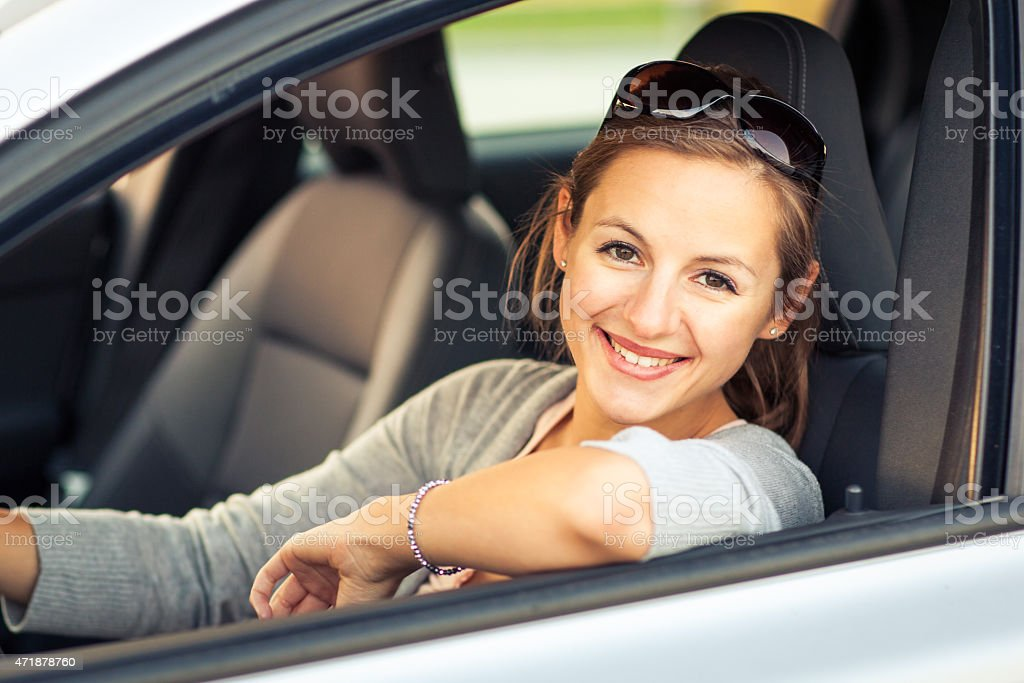 Young woman sitting inside a car with the window down stock photo