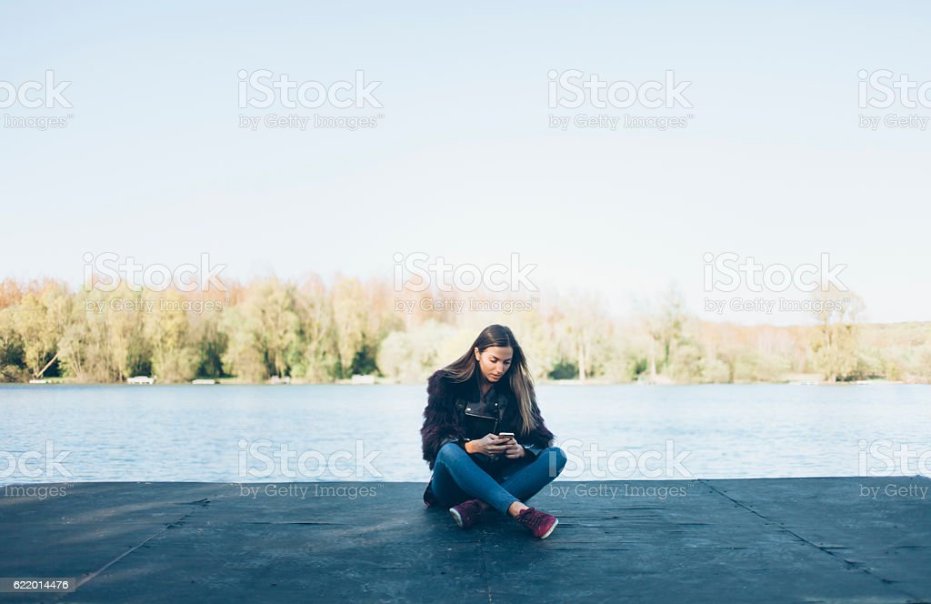 Young woman sitting legs crossed and using smart phone stock photo