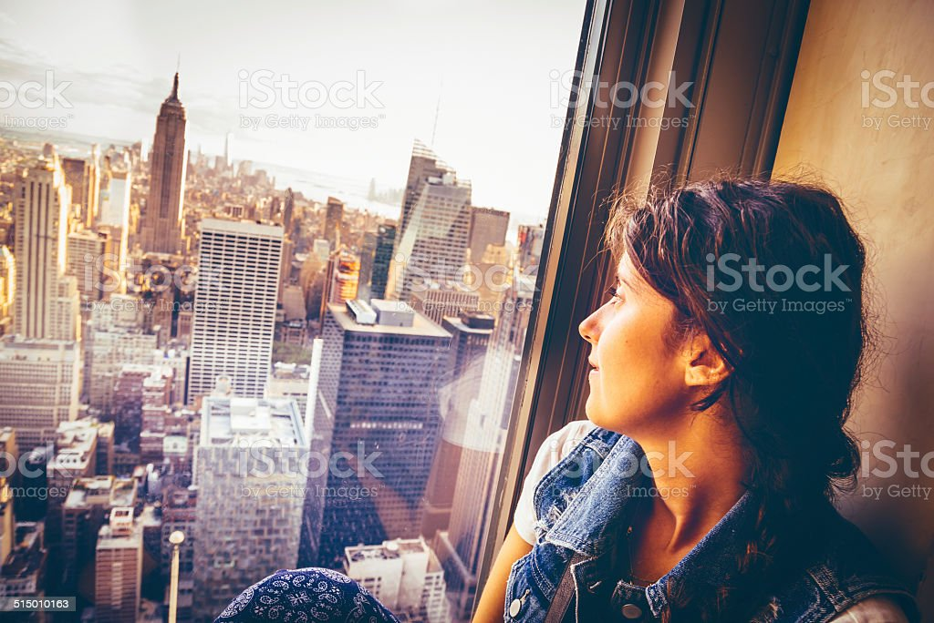 Young woman sitting near a window in New York stock photo