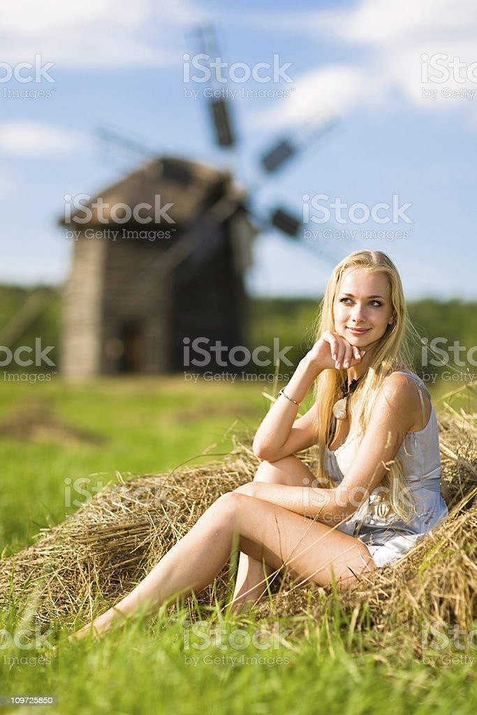 Young Woman Sitting Near Windmill royalty-free stock photo