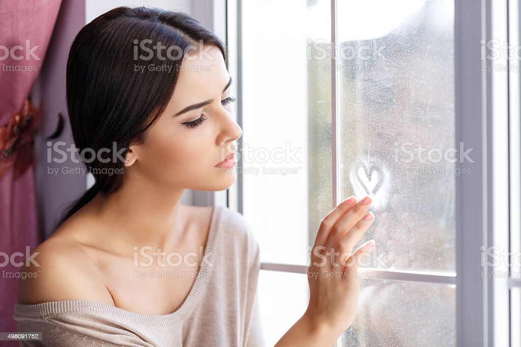 Young woman sitting near window stock photo