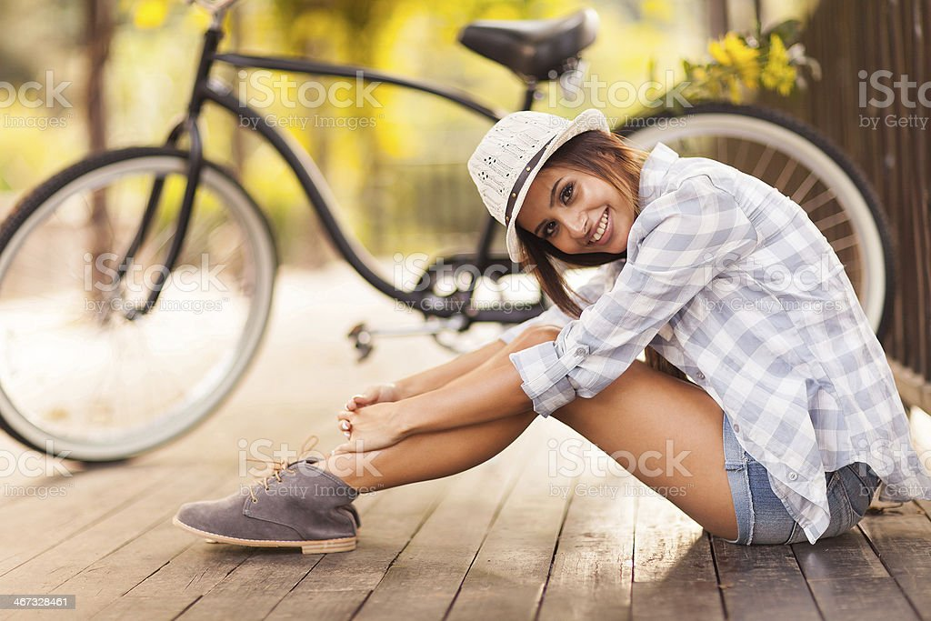young woman sitting next to her bike outdoors stock photo