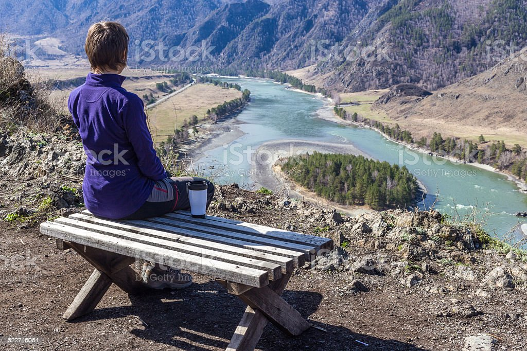 Young woman sitting on a bench and looking at river stock photo
