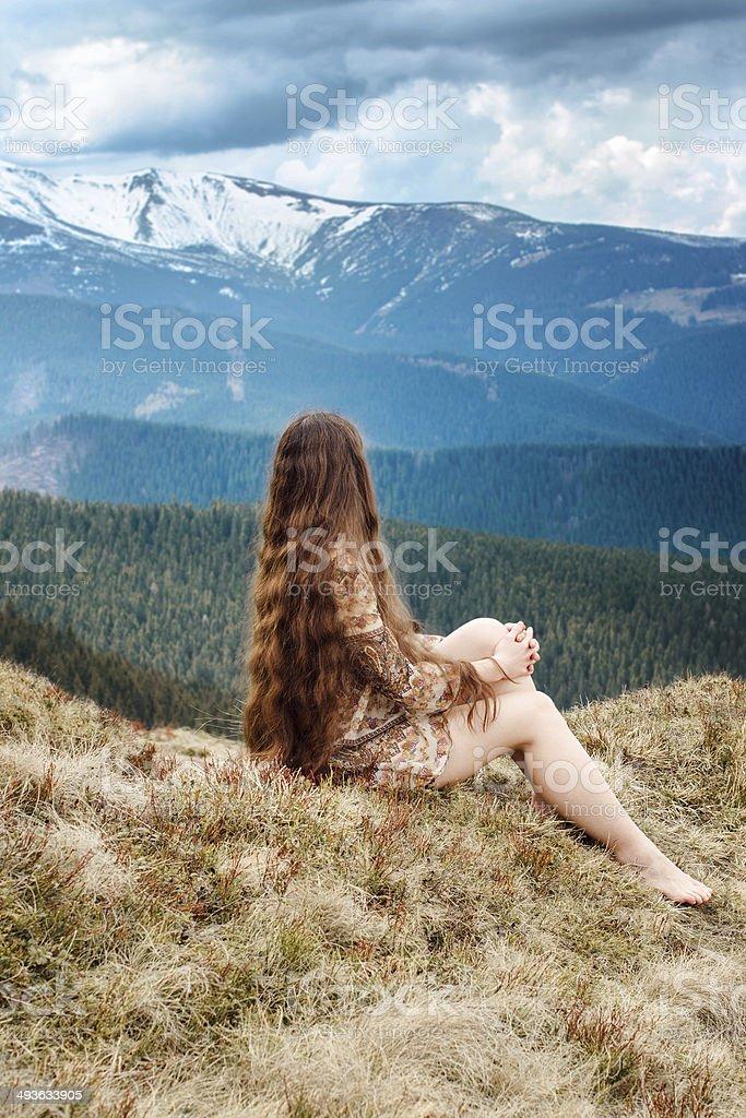 Jeune femme assise sur une colline dans des montagnes photo libre de droits