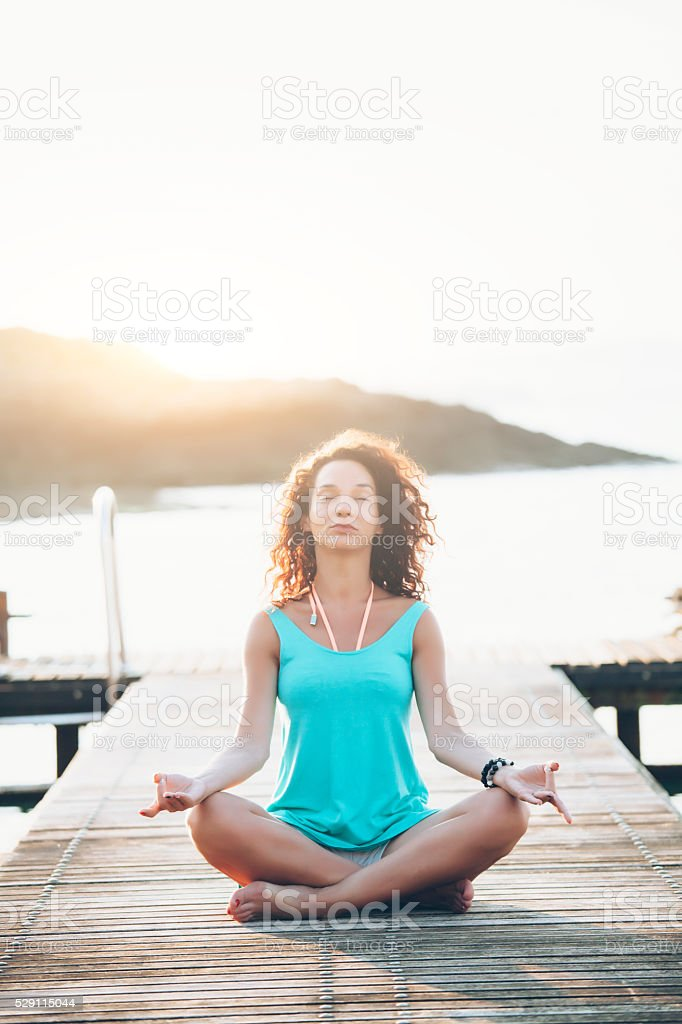 Young woman sitting on a pier in lotus pose stock photo