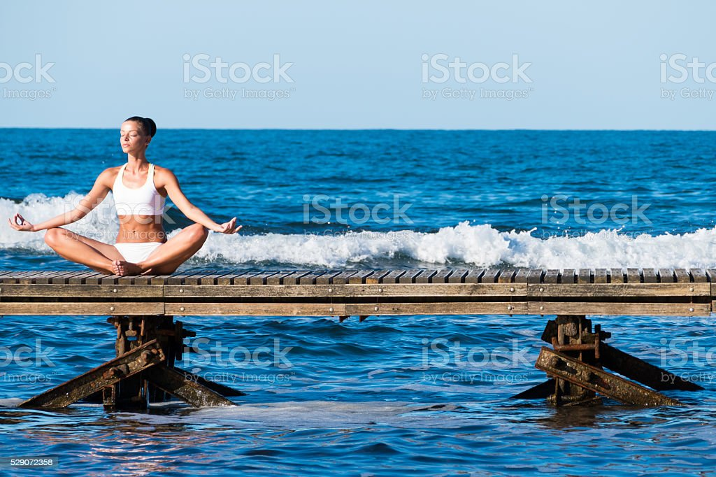 Young woman sitting on a pier in lotus position stock photo