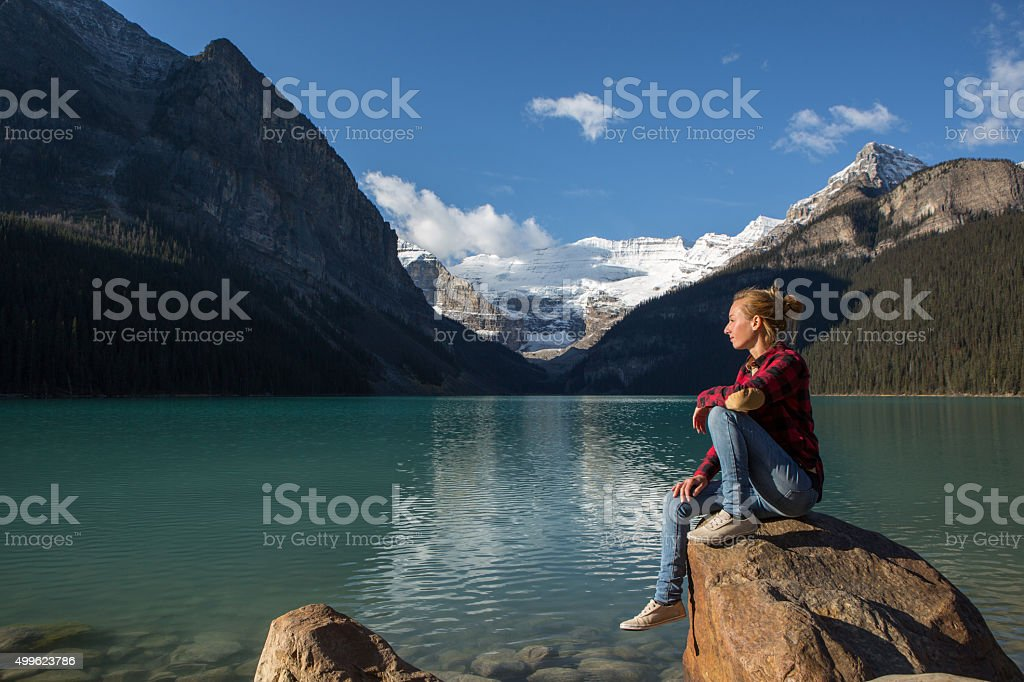 Young woman sitting on a rock by the lake relaxing stock photo