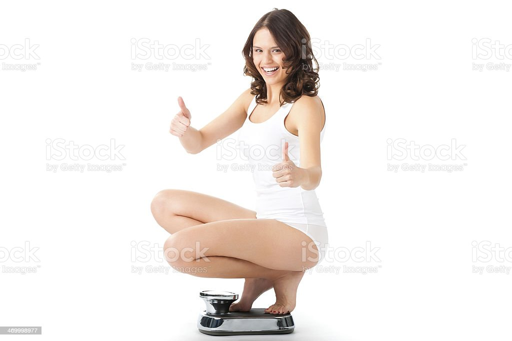 Young woman sitting on a scale stock photo