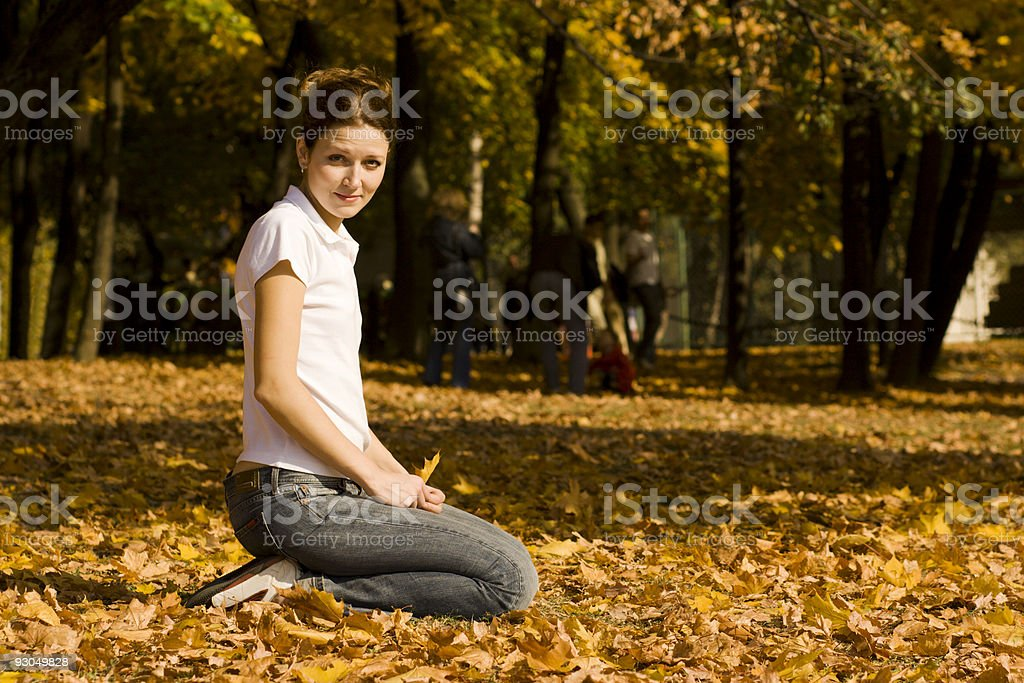Young woman sitting on autumn leaves in park royalty-free stock photo