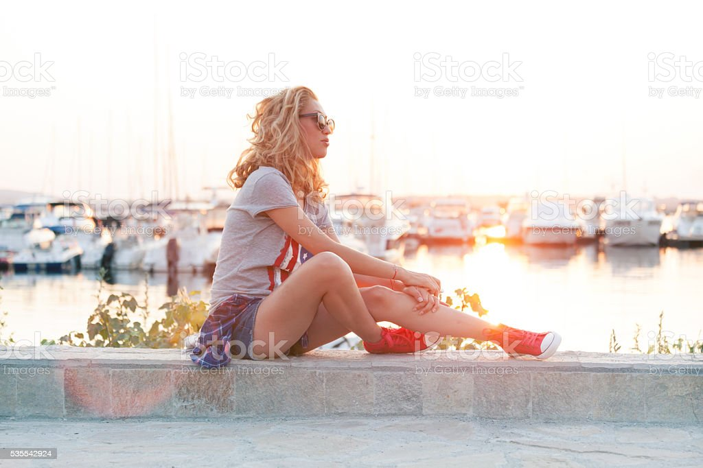 Young woman sitting on balustrade at harbor stock photo
