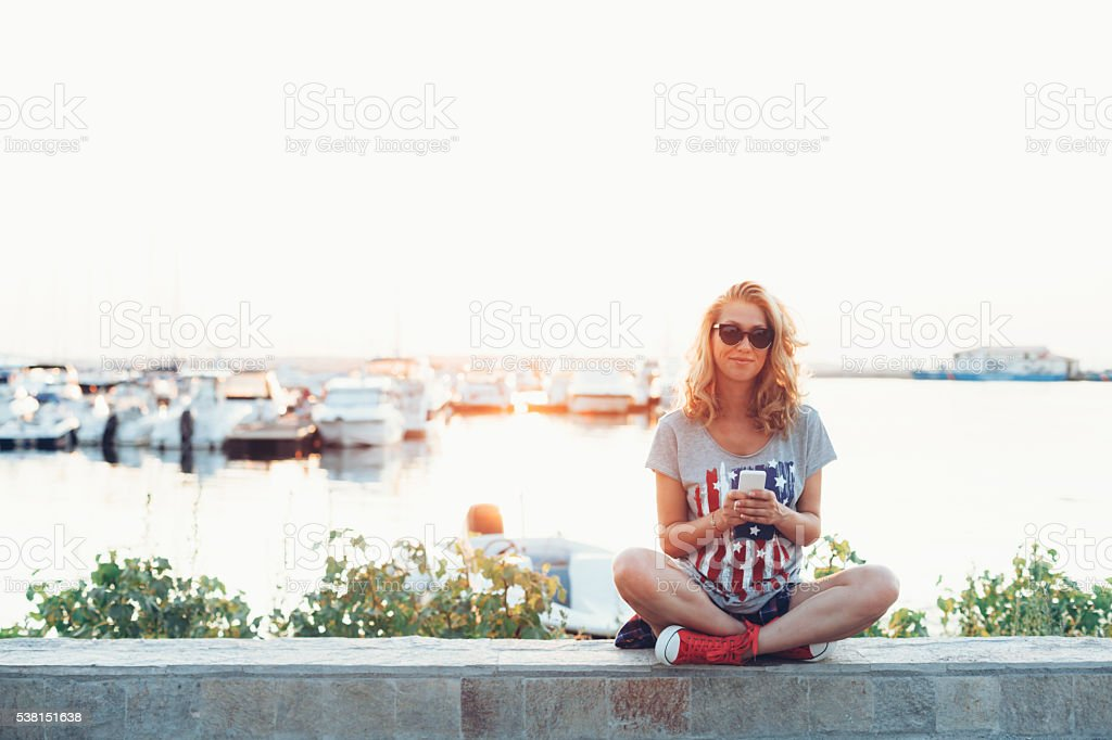 Young woman sitting on balustrade at sea and using phone stock photo