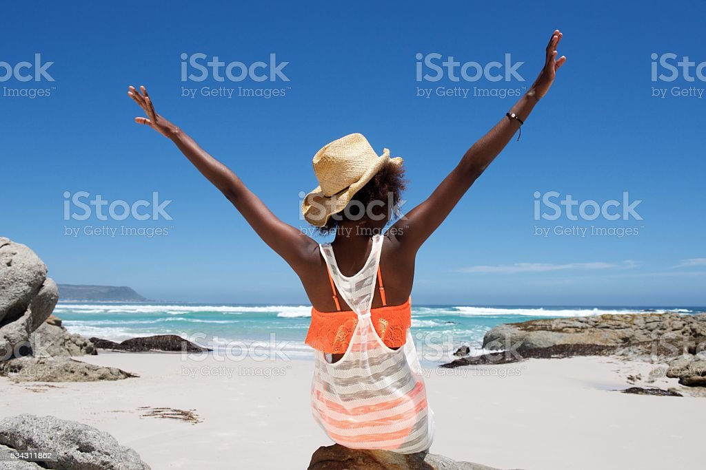 Young woman sitting on beach with her hands outstretched stock photo