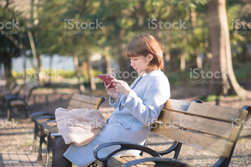 Young woman sitting on bench and watching screen on tablet stock photo