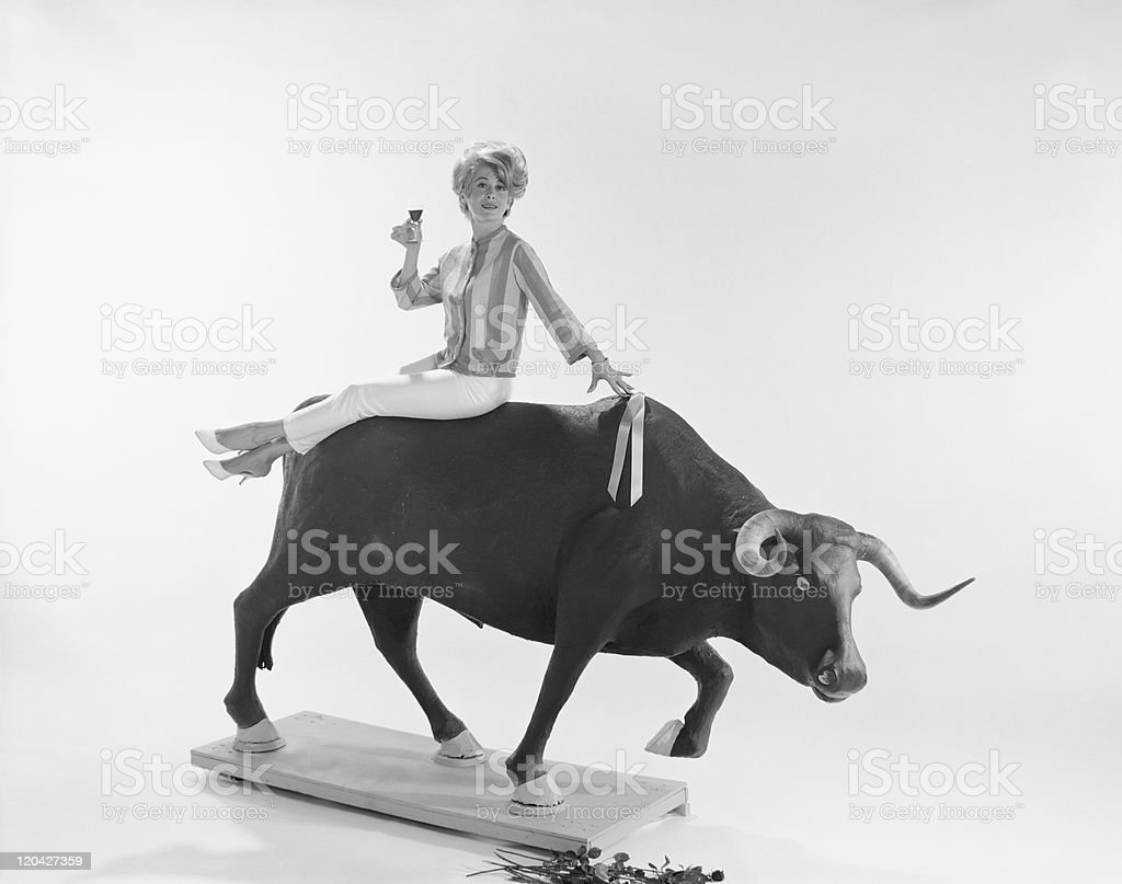 Young woman sitting on charging bull, smiling, portrait royalty-free stock photo