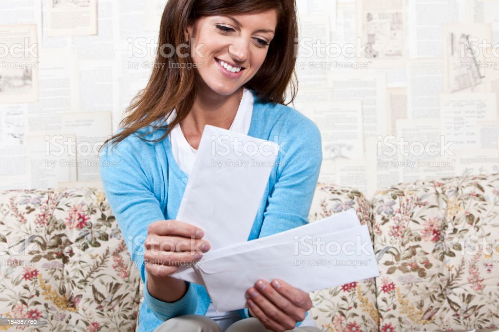 Young woman sitting on couch looking through mail stock photo