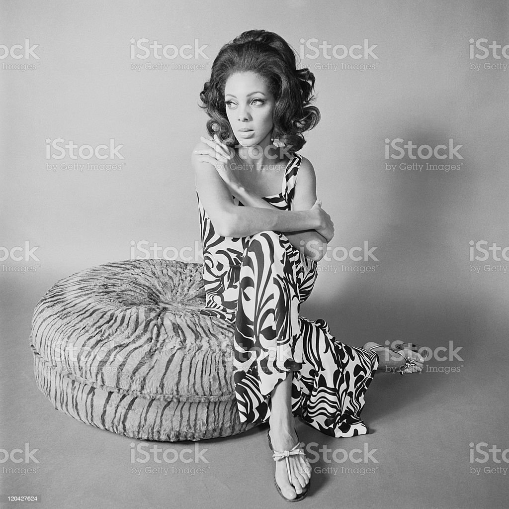 Young woman sitting on cushion stock photo