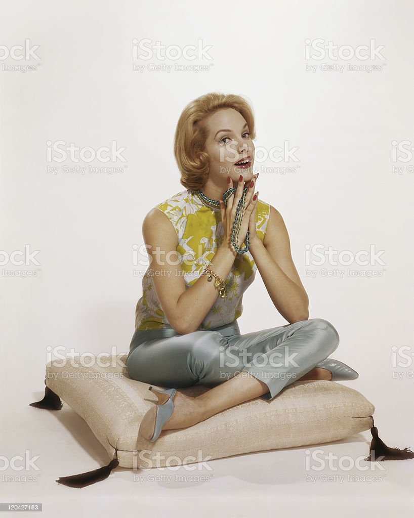Young woman sitting on cushion, smiling, portrait stock photo