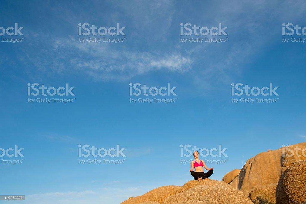 Young woman sitting on desert rocks meditating stock photo