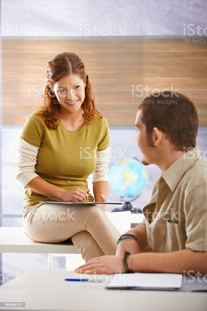 Young woman sitting on desk in classroom royalty-free stock photo